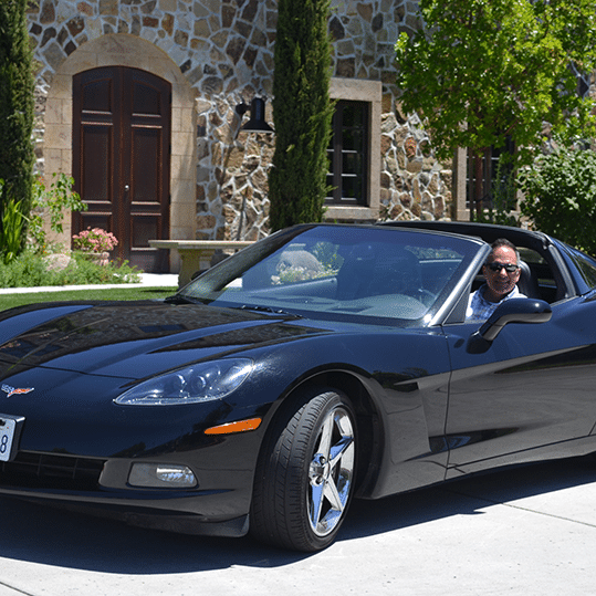 Paul in a black Chevy Corvette with T-top roof waiting on you to join him for coffee to begin your business transformation.
