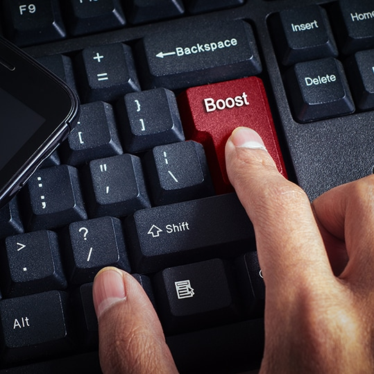 """computer keyboard closeup with red enter button with """"BOOST"""" label symbolizing the decision to boost business growth"""