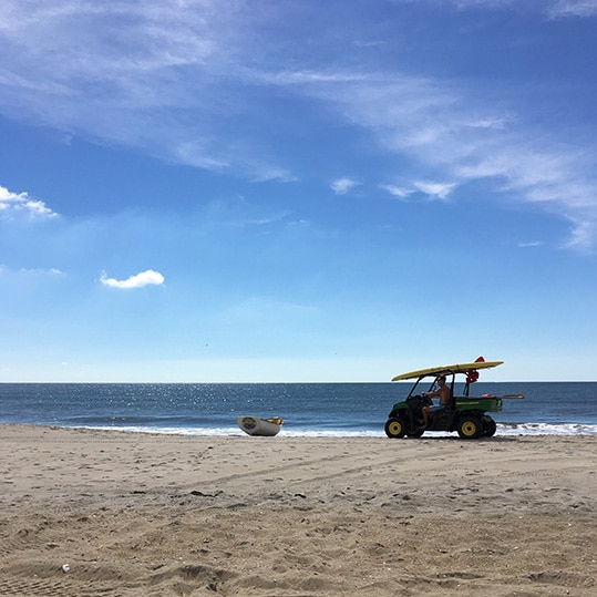 Beach scene with clear blue sky, boat, and lifeguard in ATV/surfboard symbolizing the sky is not the limit for success